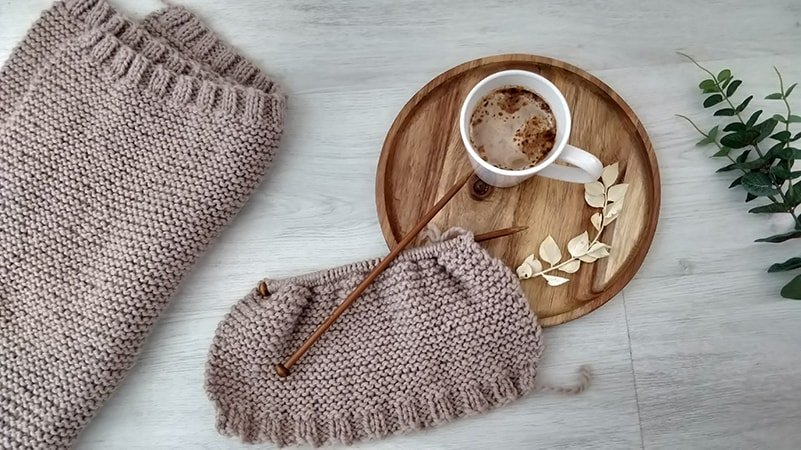 easy knitting patterns for beginners knitted sweater in progress next to a tray with coffee