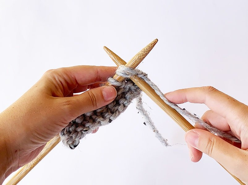 inserting the needles into the next two stitches