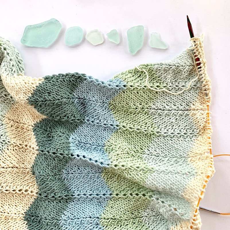 knitted shawl on the needles with pieces of sea glass