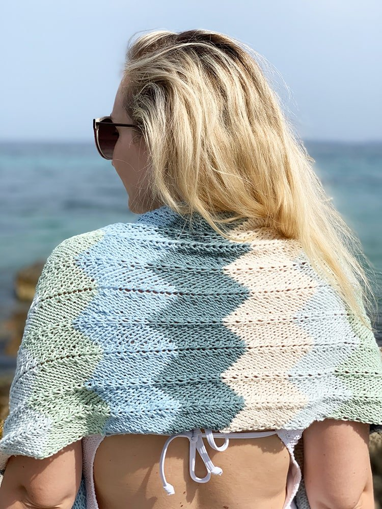 back view of a wwoman at the beach wearing a chevron patterned knit shawl