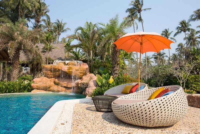 outdoor patio furniture next to a pool and waterfall