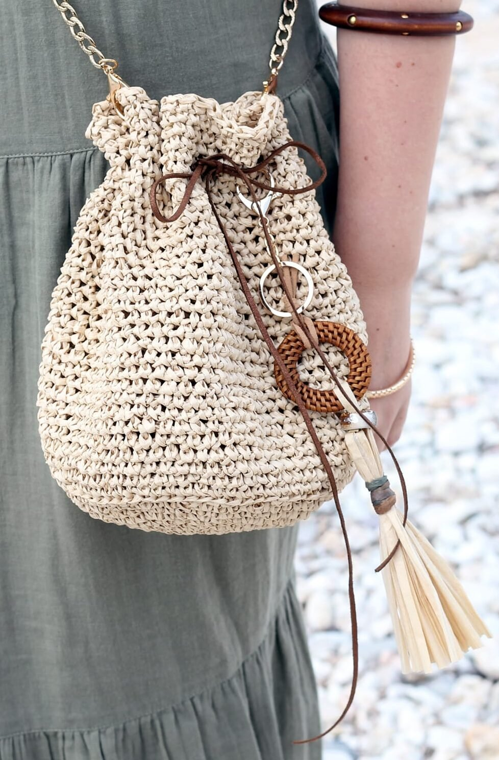 girl wearing a raffia bag at the beach with a long tassel