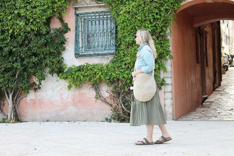 Woman wearing a large circle raffia bag across her body.