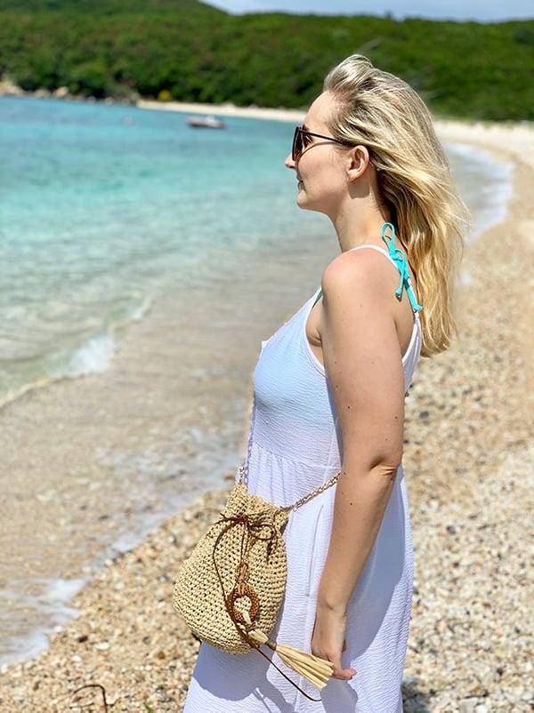 woman wearing a white dress and a raffia bag at the beach