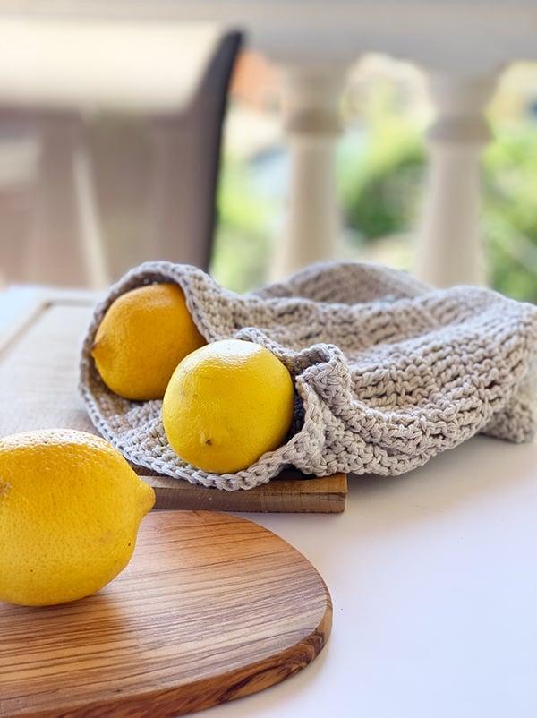 lemons on a cutting board with a crochet produce bag
