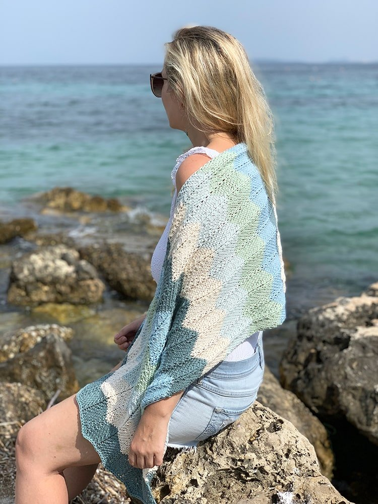 woman sitting on a rock at the beach wearing a knitted wrap in sea glass colours
