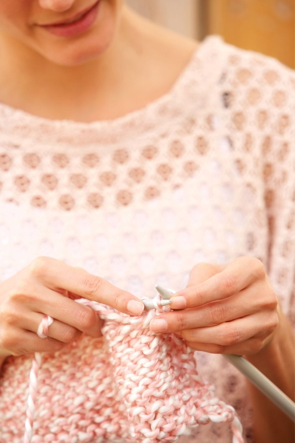 woman knitting with pink yarn
