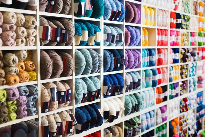knitting for beginners starts with choosing yarn from yarn filled shelves